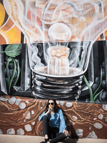 woman in front of Mural