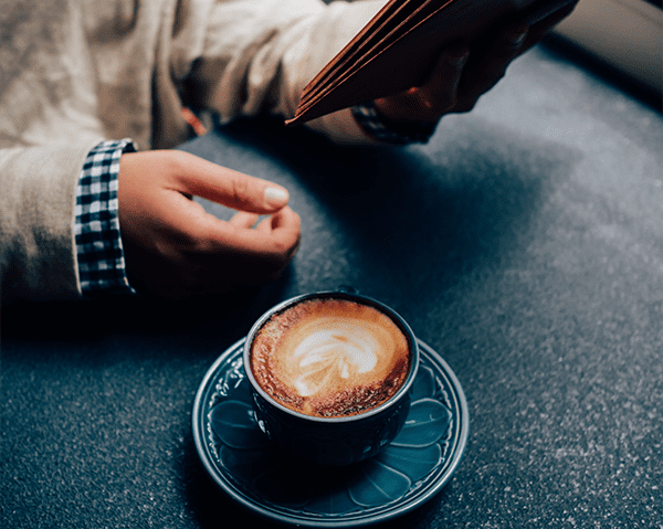 person enjoying coffee and a book
